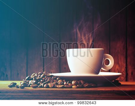 Cup of coffee with coffee beans on a beautiful brown background.Filtered image: cool cross processed vintage effect.