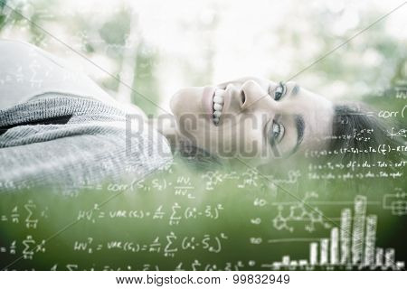 Maths equations against pretty brunette lying on the grass