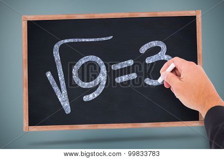 Hand writing with chalk against square root of three