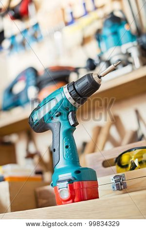Cordless drill on the table in a carpentry workshop or garage.