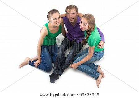 Photo of smiling friends sitting on the floor