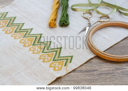 Ukrainian embroidery on the linen fabric and thread embroidery on a wooden table, selective focus