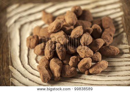 Dark chocolate truffles with almonds on wooden background