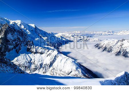 Fog Flows In A Snowy Valley Between Mountains