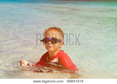 little boy swimming holding shell on beach