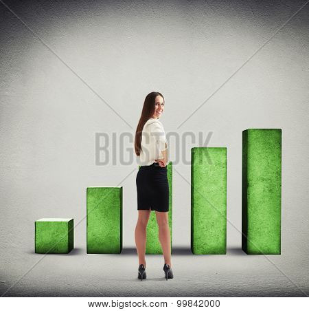 smiley businesswoman turning back and looking at camera over green diagram