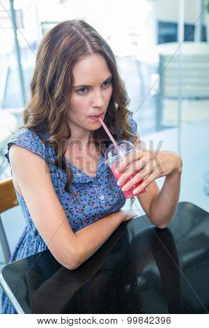 Pretty brunette sipping on a smoothie in a coffee shop
