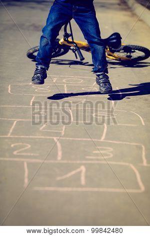 little boy playing hopscotch with bike outside