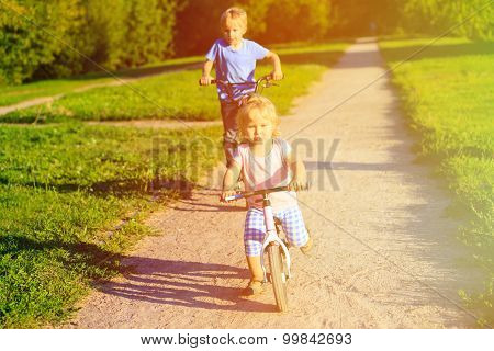 kid riding bikes in summer park