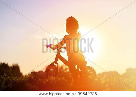 little girl riding bike at sunset