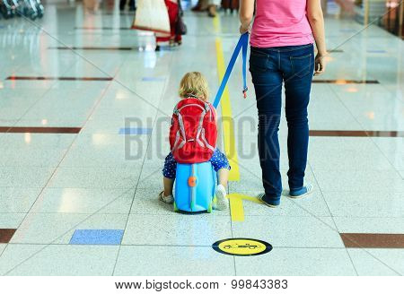 mother and little daugther walk in the airport