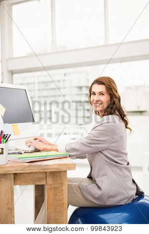 Portrait of casual businesswoman sitting on exercise ball while working in the office