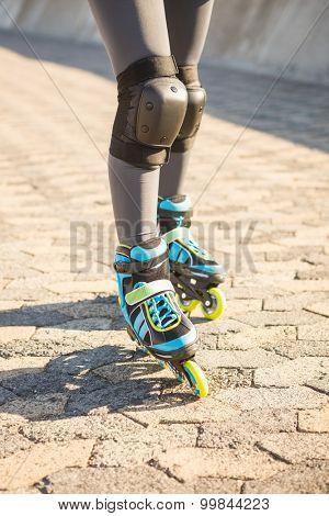Close up view of woman wearing inline skates at promenade