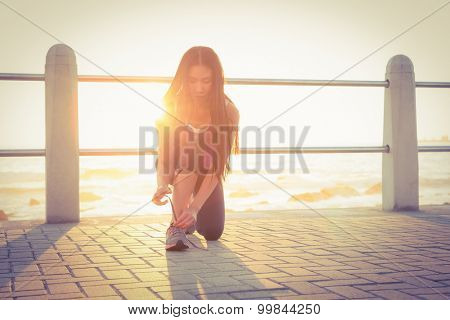 Fit woman tying her shoelace at promenade on a sunny day