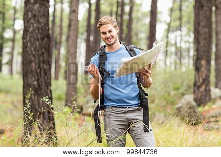 Young handsome hiker using map and compass in the nature