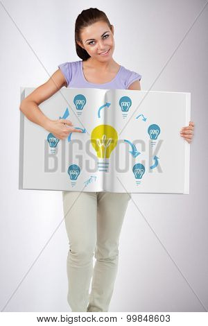Pretty woman showing a book against grey background