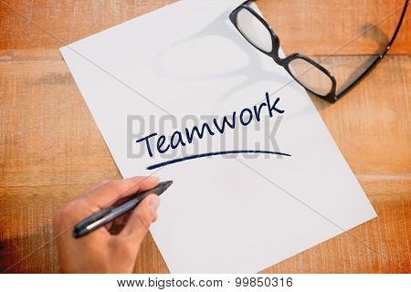 The word teamwork against left hand writing on white page on working desk