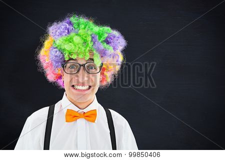 Geeky hipster wearing a rainbow wig against blackboard
