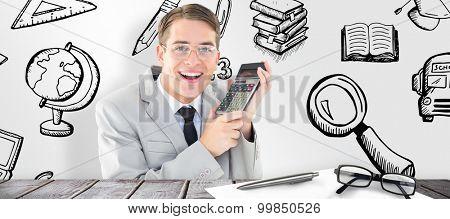 Geeky smiling businessman holding calculator against desk