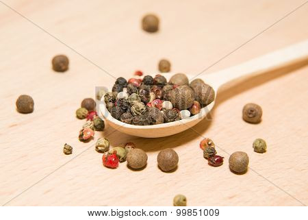 Spoon Filled With Grains Of Pepper  On A Wooden Surface