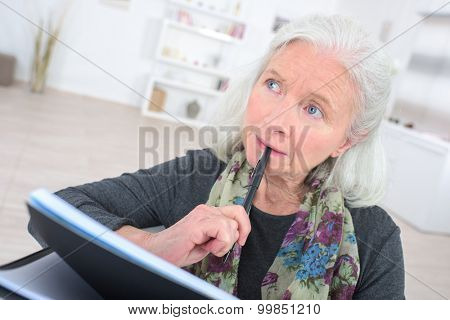 Pensive senior  with a notepad