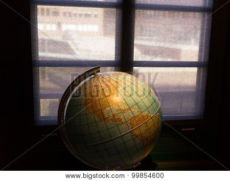 Geographic Globe In The Dark Room Against A Window