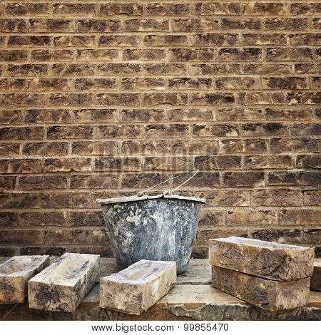 Grungy textured brown brick wall. Bucket with masonry cement and several bricks at foreground. Space for text.
