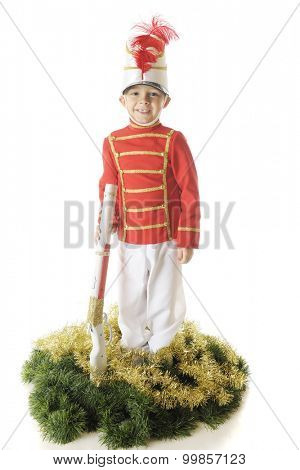 An adorable preschool Christmas soldier smiling as he stands straight and tall with his rifle.  He's surrounded by green and gold garland.  On a white background.