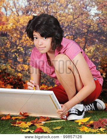 A pretty young teen looking up from her canvas as she sits on the grass while painting on a warm autumn day.