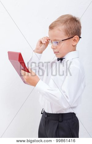 Portrait of teen boy with calculator on white background