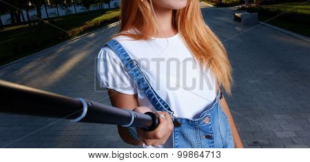 Young girl is taking selfie picture outdoors using selfie stick.