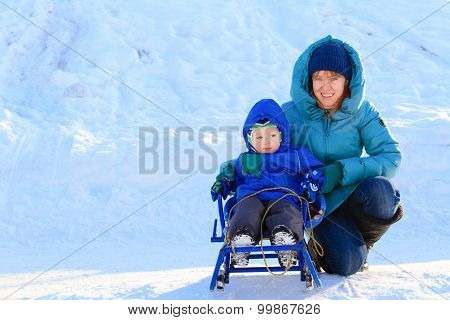 mother and son on sledge in winter