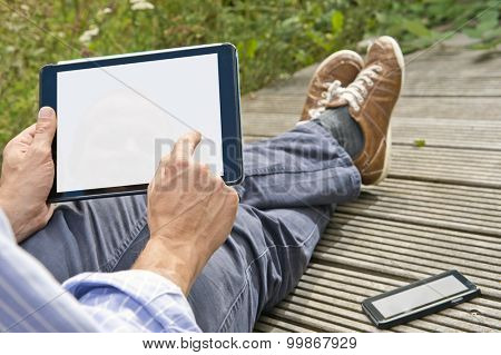 Man, tapping on a tablet, playing a game outdoors, sitting on a plank bridge, whith his phone next to him. Both can be used as presentation for mock-up apps, website and presentations.