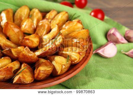 Baked potato wedges on green napkin, closeup