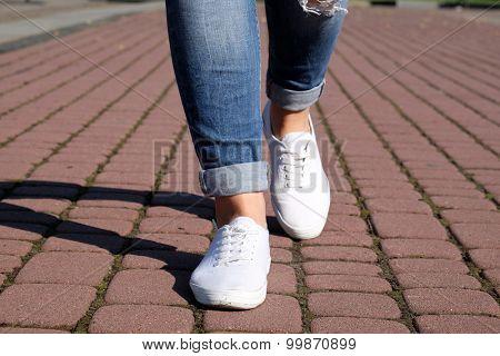 Female feet on paving stone background