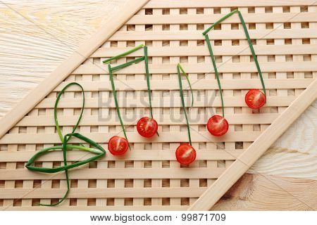 Treble clef and musical notes of green onion with tomato on striped background