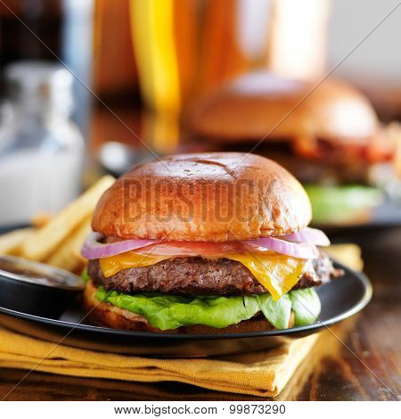 cheeseburgers and beer served with fries on wooden table top at restaurant
