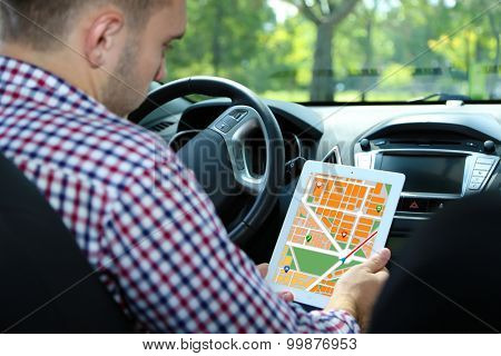 Man sitting in the car and holding tablet pc with map gps navigation application