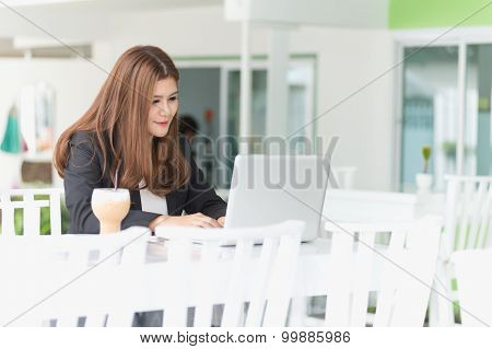 Asia Young Business Woman Sitting In A Cafe With Iced Coffee And Labtop