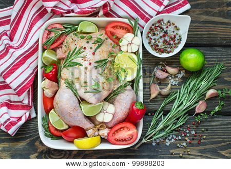 Raw chicken ready for roasting with vegetables - tomatoes, garlic, lemon, pepper and rosemary