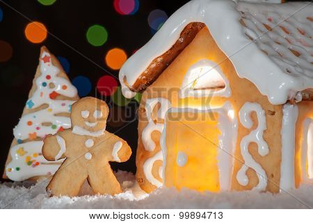 Gingerbread House With Gingerbread Man And Christmas Trees. Gingerbread Man Cookie Behind The Door.