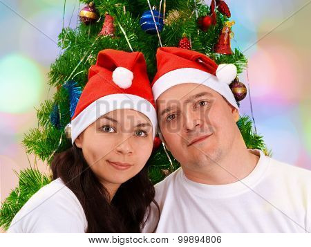 Portrait Of The Young Happy Smiling Couple Near Green Decorated Christmas Tree Wearing A White T-shi
