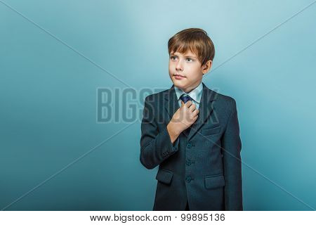 a boy of twelve European appearance in a suit straightens his ti