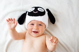 stock photo of baby sheep  - cute baby in a sheep hat lying on soft blanket - JPG
