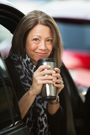 stock photo of thermos  - Cheerful mature adult woman holding coffee thermos - JPG