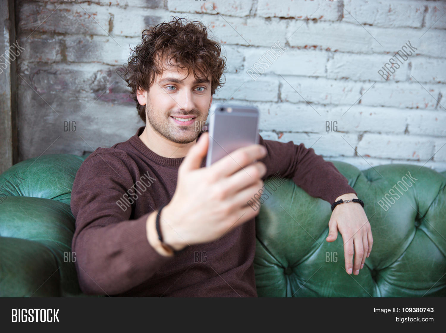 Curly handsome attractive smiling happy content guy in brown ...