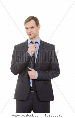 body language. man in business suit isolated on white background. straightens his tie, flirting