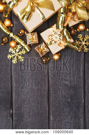 Christmas gift boxes with gold Christmas decoration on wooden background with empty place for the text