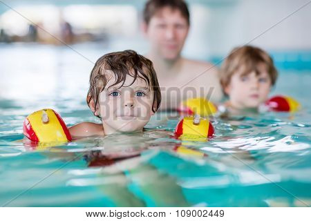 Young dad teaching his two little sons to swim indoors