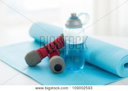 sport, fitness, healthy lifestyle and objects concept - close up of bottle with water, dumbbells and sports mat